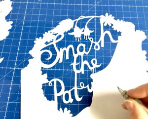 """Emma's hand holding a scalpel in the process of papercutting. The papercut reads """"Smash the Patriarchy"""" and is cut from white paper on a bright blue cutting mat background."""